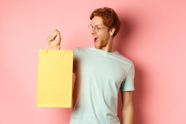 ピンクの背景の上に立って、プレゼントを買って、買い物袋を持って、面白がって見えるハンサムな若い男
