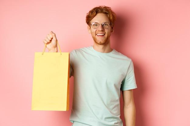 Красивый молодой человек покупает подарки, держит сумку и улыбается в камеру, стоя на розовом фоне.
