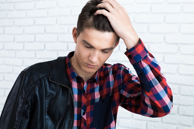 Handsome young man in casual clothes, standing against white brick wall