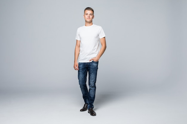 Handsome young man in a casual style clothing white t-shirt and blue jeans on white