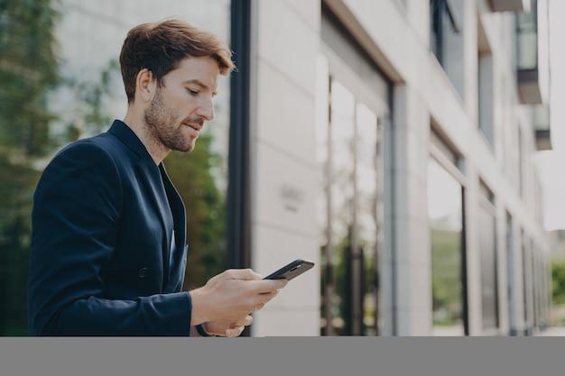 Красивый молодой человек разговаривает и просматривает веб-страницы на своем телефоне, стоя на открытом воздухе