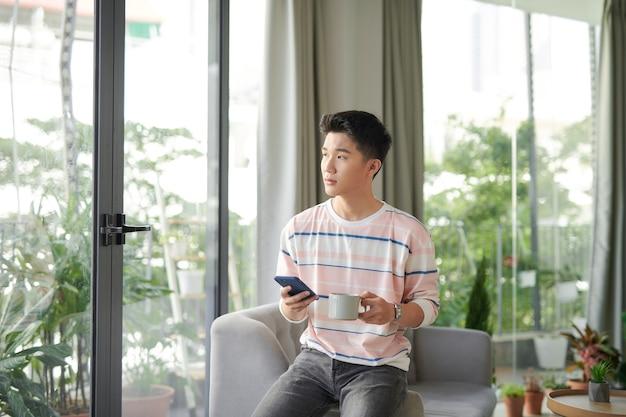 Красивый молодой человек проверяет свои сообщения, попивая кофе дома