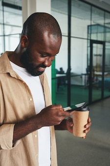 Handsome young man checking his smartphone during coffee break