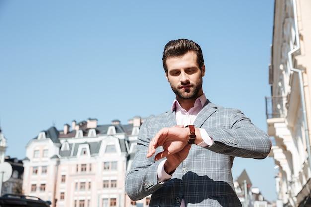 Красивый молодой человек, проверка времени на его наручные часы