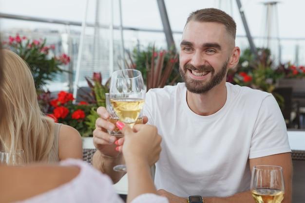 屋上レストランでデート中にガールフレンドとメガネをチリンと鳴らすハンサムな若い男