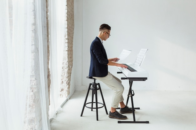 Handsome young man in coat looking at musical sheet playing on keyboard