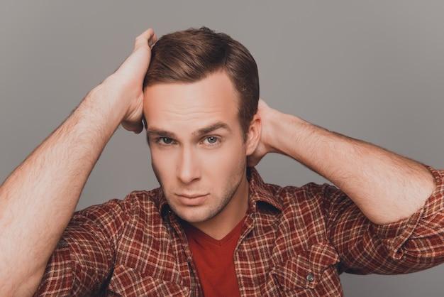 Красивый молодой человек, расчесывающий волосы пальцами