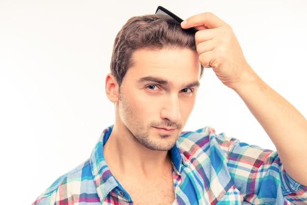 Красивый молодой человек, расчесывающий волосы