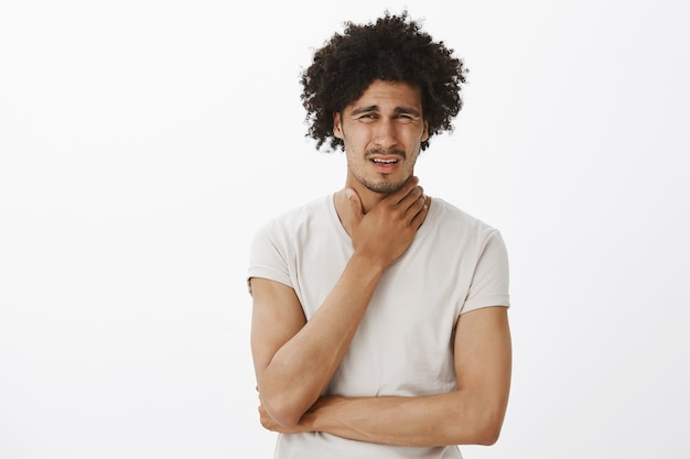 Handsome young man complaining on sore throat, got sick