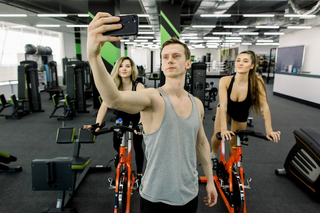 Handsome young man couch making selfie on the phone in gym, while two young pretty girls training on exercise bikes together in fitness club