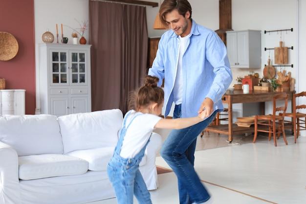 彼の小さなかわいい娘と一緒に家で踊るハンサムな若い男。