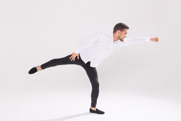 Красивый молодой человек танцует на белой стене