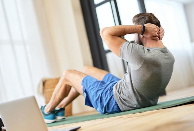 Красивый молодой человек делает упражнения на пресс дома