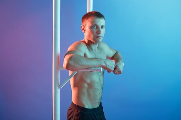 横棒の運動をしているハンサムな若い男