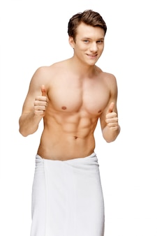 Handsome young man doing morning hygiene procedures isolated on white