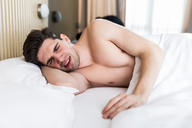 Handsome young man dreaming and sleeping on pillow in bed