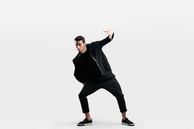 黒い服を着たハンサムな若い男がストリートダンスを踊っています