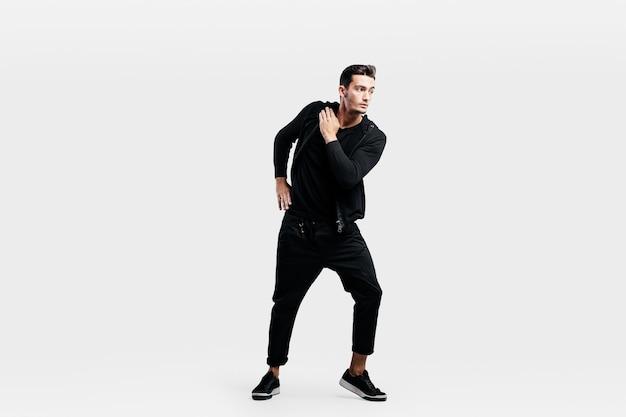 スポーツの黒い服を着たハンサムな若い男がストリートダンスを踊っています