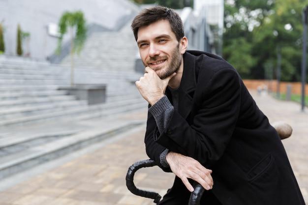 Красивый молодой человек, одетый в пальто, опираясь на велосипед на улице