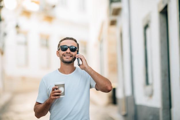 電話で会話をしている街の通りで流行の服を着たハンサムな若い男