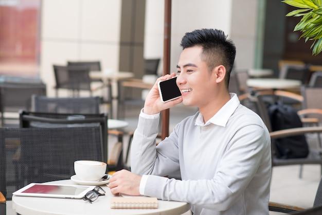 ハンサムな若い男がコーヒーを飲み、市で電話で