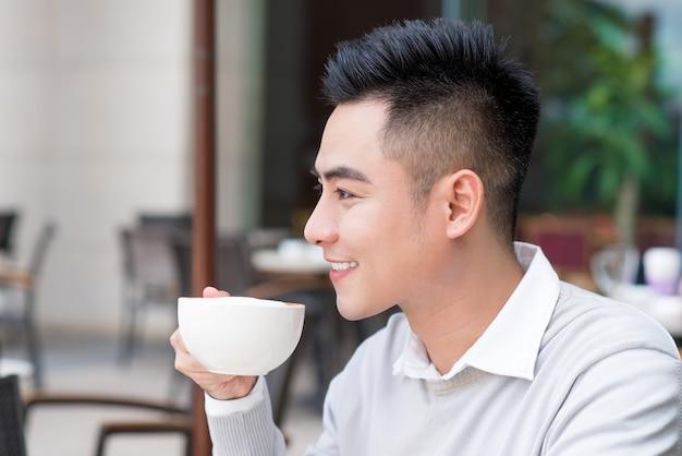 도시에서 커피를 마시는 잘 생긴 젊은 남자