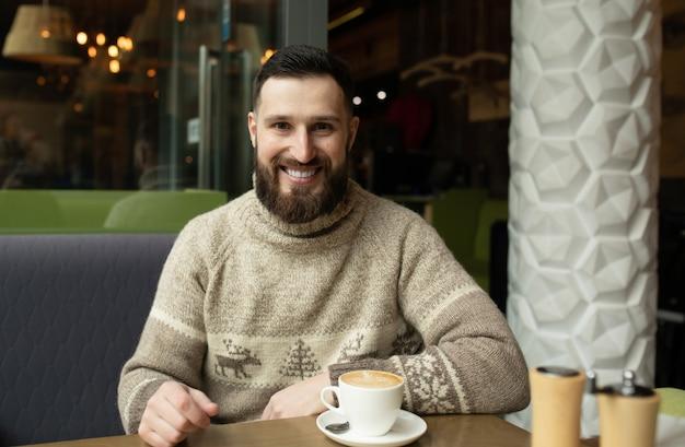 ハンサムな若い男が喫茶店でコーヒーを飲む