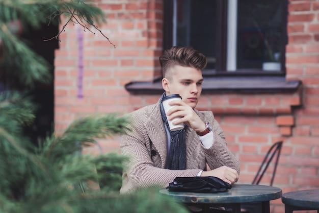 屋外でコーヒーを飲みながらハンサムな若い男