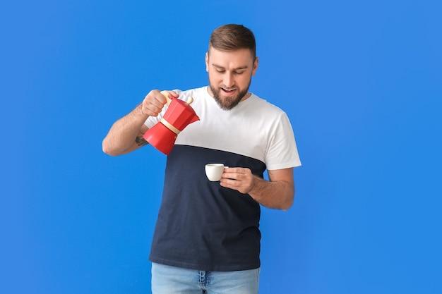 색상 공간에 뜨거운 커피를 마시는 잘 생긴 젊은 남자