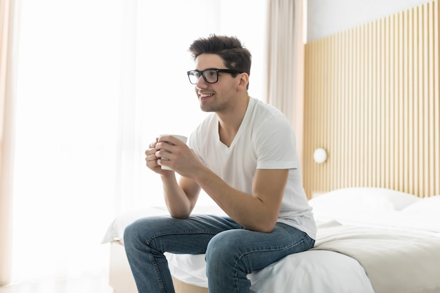 Handsome young man drinking morning coffee in the bed