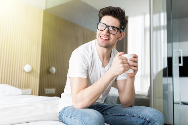 Красивый молодой человек, пить утренний кофе в постели