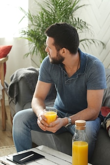 Handsome young man drinking orange juice at home