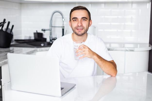 ハンサムな若い男が台所でノートパソコンでの作業中に水を飲む