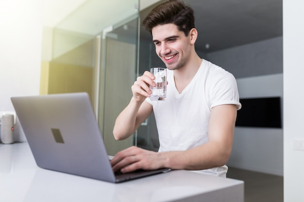 Handsome young man drinking water while working with laptop in kitchen at home