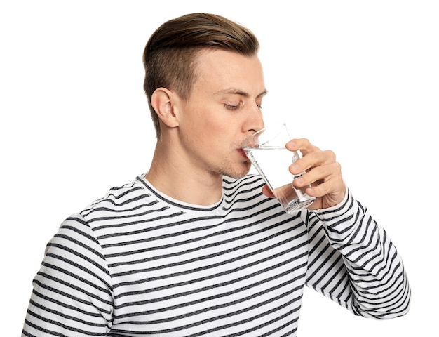 Handsome young man drinking water on white