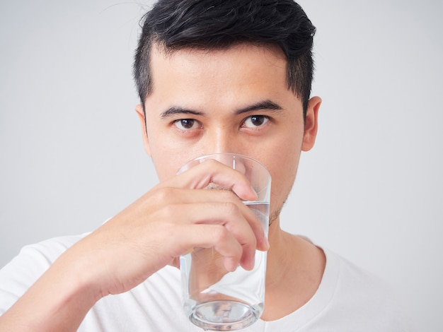Handsome young man drinking water