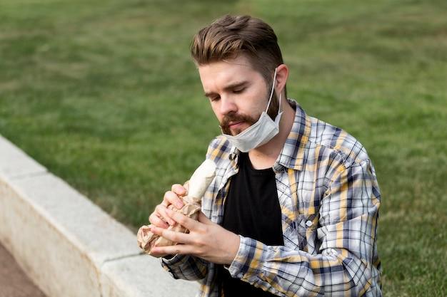 Красивый молодой человек ест шашлык