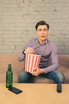 Красивый молодой человек ест попкорн и смотрит телевизор