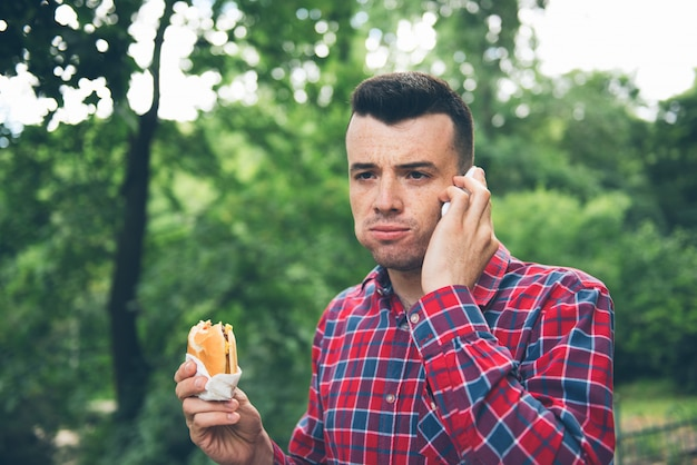 Handsome young man eating sandwich outdoor