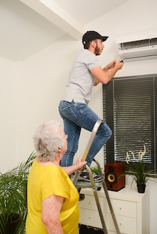 Handsome young man electrician cleaning air filter on an indoor unit of air conditioning system in a client house with senior woman