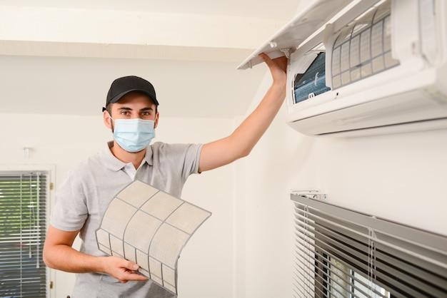 クライアントの家の空調システムの屋内ユニットのエアフィルターを掃除するサージカルマスクを持つハンサムな若い男の電気技師