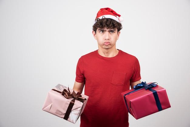Bel giovane sentirsi annoiato con scatole regalo.