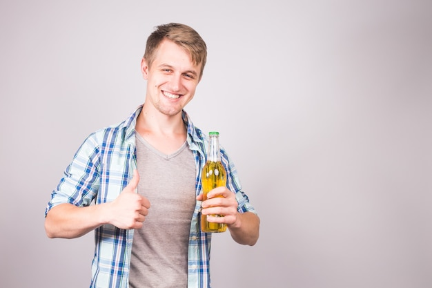 A handsome young man feeling happy showing thumbs up and holding a bottle of beer.
