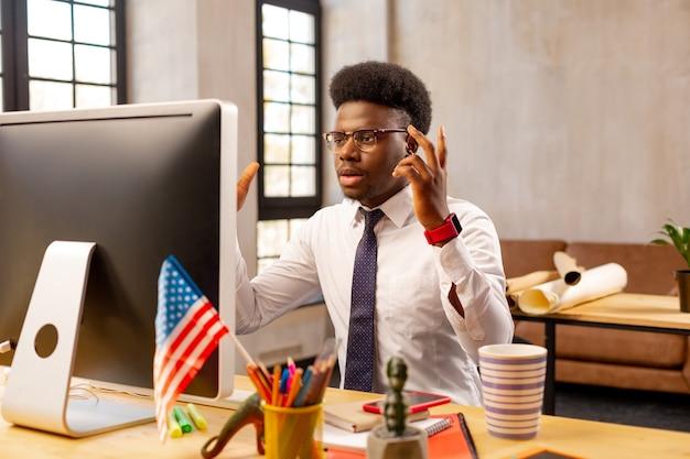 仕事で問題を抱えている間、怒っているハンサムな若い男