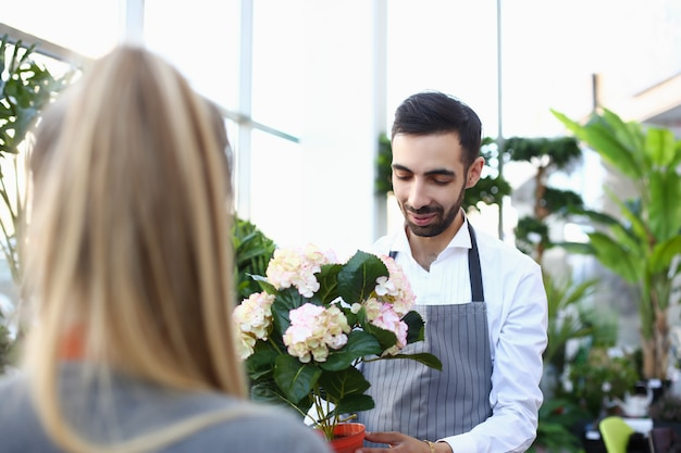 Handsome young man giving flower to lady in plant store