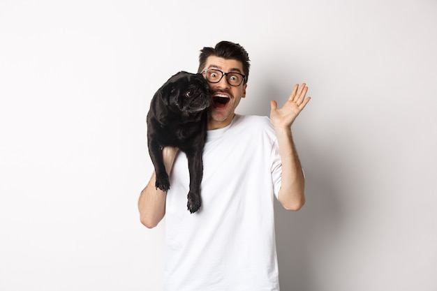 Handsome young man in glasses holding his black pug and waving hand, guy saying hello while carry dog with one arm, standing over white background