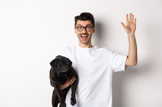 Handsome young man in glasses holding his black pug and waving hand, guy saying hello while carry dog with one arm, standing over white.