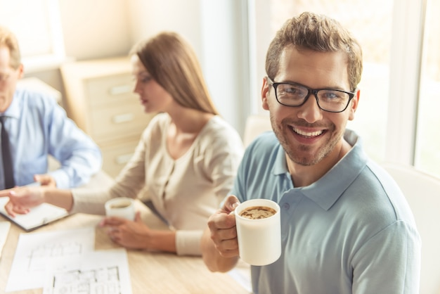 Handsome young man in glasses is holding cup of coffee.
