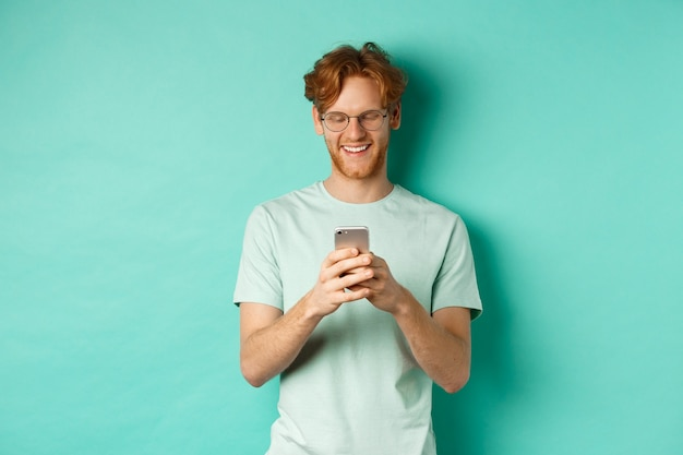 Handsome young man in glasses with red messy hair reading message on mobile phone, smiling and looking at screen, standing over mint background.