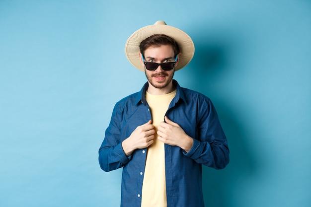 休暇に行くハンサムな若い男、シャツを調整し、サングラスと麦わら帽子をかぶっています。夏休みのコンセプト。
